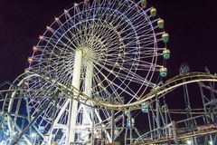 Ferris wheel and roller coaster track. Theme park in the philippines Stock Photos
