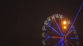 Ferris wheel rotating at amusement park under dark night sky stock footage