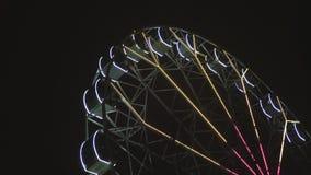 Ferris wheel rotating at amusement park under dark night sky stock video