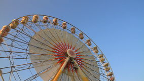 Ferris wheel rotating with blue sky in background stock video footage