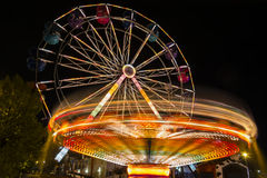 Ferris wheel and roundabout. Blurs and color effects created by the Ferris wheel and roundabout at the amusement park Stock Image