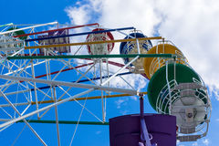 Ferris wheel seats against blue cloudy sky background Stock Image