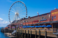 Big Wheel at Seattle Pier. Big Ferris Wheel and restaurant outdoor seating at Seattle Pier 57 stock photo