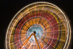 Ferris wheel spinning colors. Ferris wheel at night, spinning circular colors of red, orange, yellow and blue Royalty Free Stock Photo