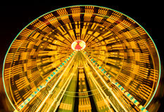 Ferris wheel spinning at fairground at night Stock Image