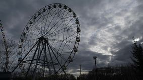 Ferris Wheel Spinning i bakgrunden av en dramatisk himmel lager videofilmer