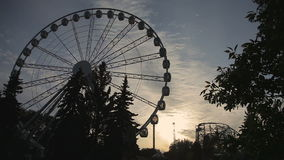 Ferris wheel at sunset. Ferris Wheel at amusement park. Ferris wheel with covered booths in white on a background of sunset. Russia, Saint-Petersburg, 2016 stock video