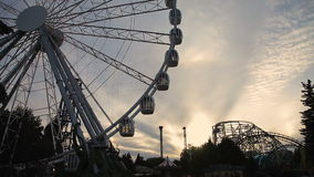 Ferris wheel at sunset. Ferris Wheel at amusement park. Ferris wheel with covered booths in white on a background of sunset. Russia, Saint-Petersburg, 2016 stock footage