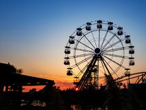 Ferris wheel in sunset. Big wheel with cabins stock image