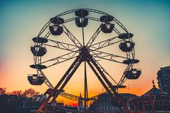 Ferris wheel at sunset - popular park attraction. Ferris wheel Silhouette at sunset against the colorful evening skyline at dusk - popular children attraction in Stock Image