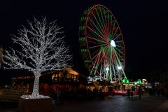 Ferris wheel and tree in lots of light at the christmas fair in stock photos