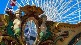 Ferris Wheel und Karussell in einen Vergnügungspark tagsüber mit heller blauer Himmel- und Weiß Riesenradfarbe Stockbilder