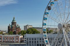 Ferris wheel and Uspenski Cathedral, an Eastern Orthodox cathedral in Helsinki, Finland. HELSINKI, FINLAND - JULY 10, 2017: Ferris wheel and Uspenski Cathedral stock images