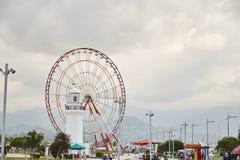 Ferris Wheel vermelho e uma estátua de um homem e de uma mulher foto de stock royalty free