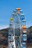 Ferris wheel. View of colorful Ferris Wheel with blue sky near mountain stock image