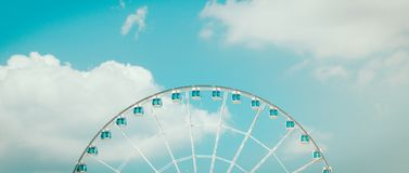 Ferris wheel and white cloud in blue pastel sky.  Stock Images