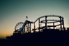 Ferris Wheel y roller coaster en la puesta del sol Fotografía de archivo