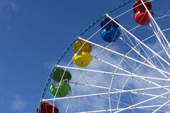 Ferris wheel, yellow, red, blue, green booths, seats, a blue sky Royalty Free Stock Photo