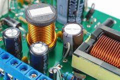 Ferrite choke and electrolytic capacitors mounted on the circuit Board royalty free stock photography