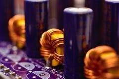 Ferrite ring. On purple circuit board, close up Stock Image