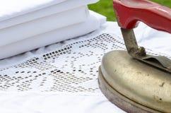 Ferro antigo com a pilha da roupa de linho Imagens de Stock Royalty Free