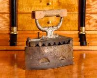 Ferro antigo de carvão na mesa antiga da madeira da cereja Foto de Stock