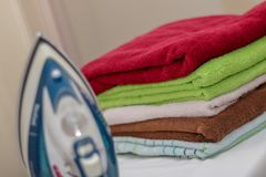 Ferro com as toalhas na tábua de passar a ferro Foto de Stock Royalty Free