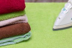 Ferro com as toalhas na tábua de passar a ferro Fotografia de Stock Royalty Free