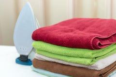 Ferro com as toalhas na tábua de passar a ferro Imagens de Stock