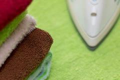 Ferro com as toalhas na tábua de passar a ferro Fotos de Stock Royalty Free