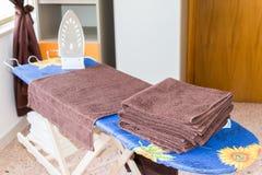 Ferro da stiro e mucchio dei vestiti sulla tavola da stiro, lavoro domestico immagine stock libera da diritti