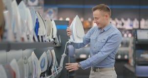 Ferro de exploração do homem considerável novo a comprar em uma loja de dispositivos elétricos vídeos de arquivo