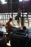 Ferro del riscaldamento del fabbro in un fuoco del carbone Immagini Stock