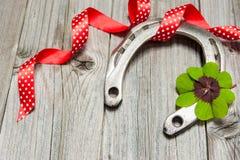 Ferro di cavallo, acetosella e nastro rosso su vecchio di legno Fotografia Stock Libera da Diritti