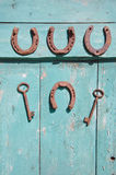 Ferro di cavallo antico e chiave arrugginita sulla vecchia porta di legno Fotografia Stock