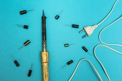 Ferro e capacitores velhos de solda em um fundo azul imagens de stock royalty free