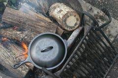 Ferro fundido que cozinha em um fogo aberto imagens de stock