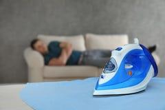 Ferro moderno ed uomo addormentato nella sala immagine stock