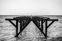 Ferro não utilizado, ponte oxidada no mar imagens de stock