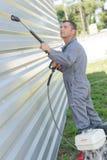 Ferro ondulado da parede da limpeza do trabalhador foto de stock royalty free
