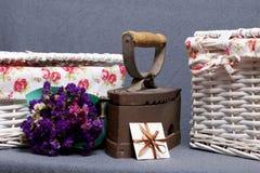 Ferro velho, aquecido por carvões quentes Localizado na tela cinzenta Estão próximo as cestas de vime, um ramalhete de flores sec foto de stock royalty free