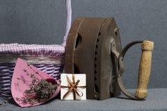 Ferro velho, aquecido por carvões quentes Localizado na tela cinzenta Estão próximo as cestas de vime, um ramalhete de flores sec imagem de stock