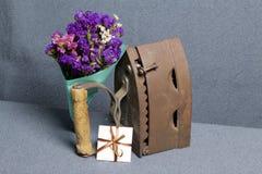 Ferro velho, aquecido por carvões quentes Localizado na tela cinzenta Estão próximo o ramalhete de flores secadas e um cartão imagens de stock royalty free