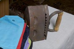 Ferro velho, aquecido por carvões quentes Localizado na tela de linho Estar em uma tábua de passar a ferro Ao lado de uma pilha d imagens de stock royalty free