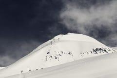 Ferrocarril aéreo en estación de esquí y cuesta fuera de pista nevosa Imagen de archivo libre de regalías