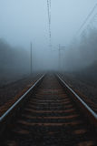 Ferrocarril al horizonte en niebla fotos de archivo