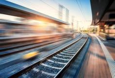 Ferrocarril con efecto de la falta de definici?n de movimiento en la puesta del sol fotos de archivo