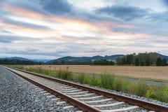 Ferrocarril con los campos y las montañas Fotos de archivo
