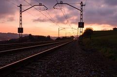 Ferrocarril contra el cielo hermoso en la puesta del sol Paisaje industrial con el ferrocarril, cielo azul colorido con las nubes fotos de archivo
