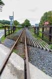 Ferrocarril del indicador estrecho o pista de ferrocarril que converge en distancia Fotografía de archivo